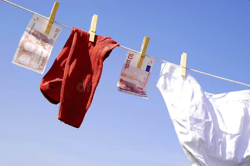 Money laundering. Photo of money and clothes hanging on the clothesline on the blue sky royalty free stock image