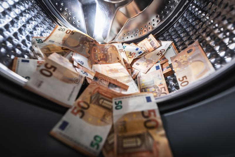 Money laundering concept - euro banknotes in washing machine royalty free stock image