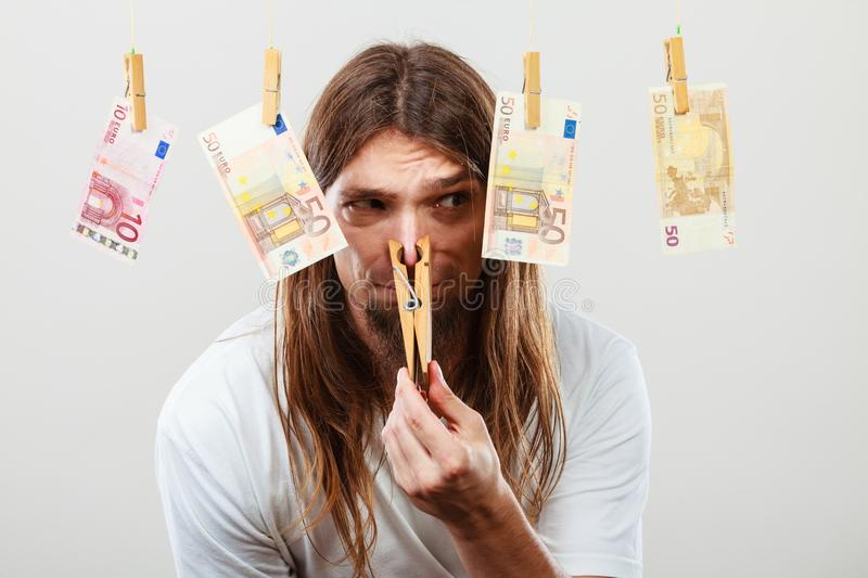 Young man sick of money. Money laundering concept. Young man with clothespin on his nose. Illegal business royalty free stock photography