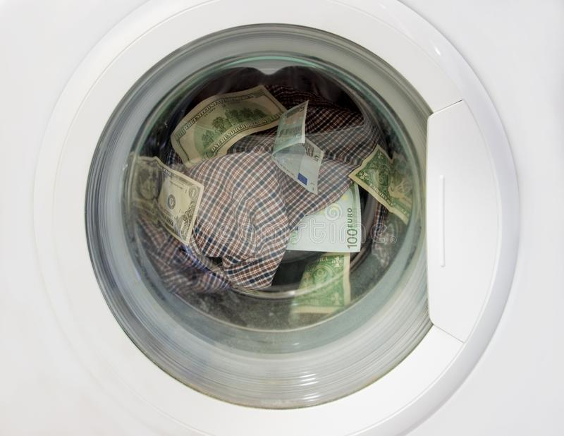Money laundering dollars and euros in a washing machine along with linens. royalty free stock photography