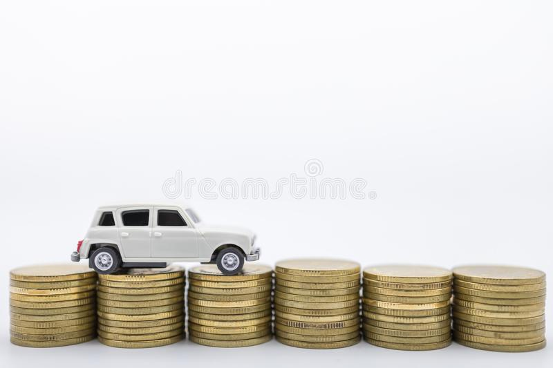 Money, Loan and Saving concept. CLose up of white miniature mini car toy on top of row of stack of gold coins on white background royalty free stock image