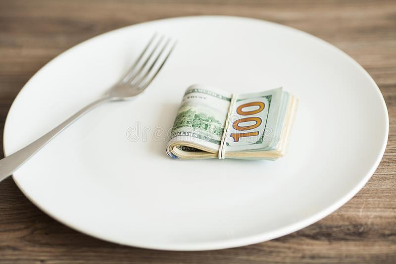 Money lying on the plate with fork. Dollars photo. Greedy corruption concept. Bribe idea stock photos