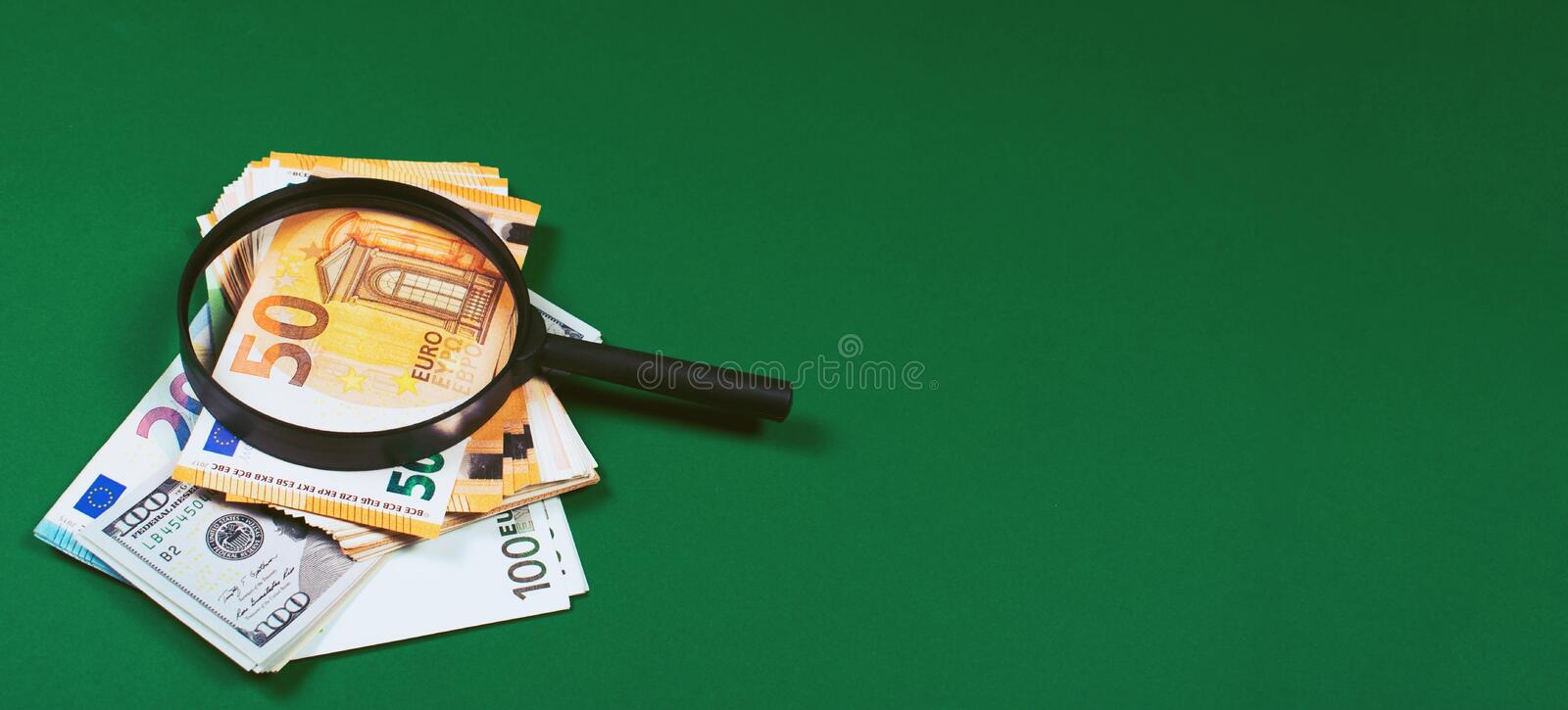 Money and magnifying glass on green background royalty free stock images