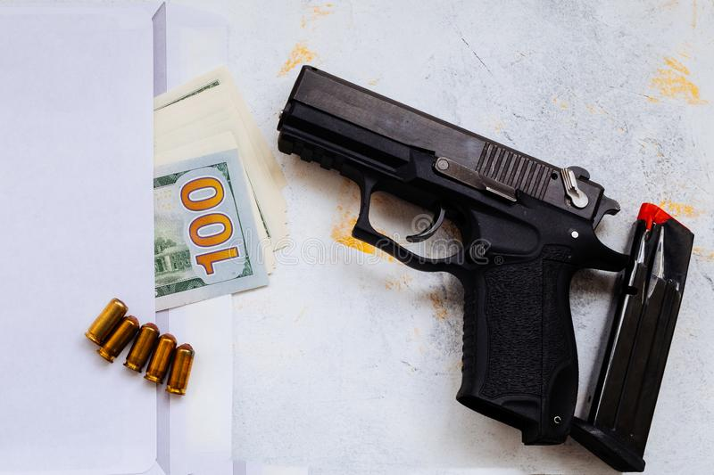 Money for murder. Black gun on American dollars background. Military industry, war, global arms trade, weapon sale, contract. Killing and crime concept stock images