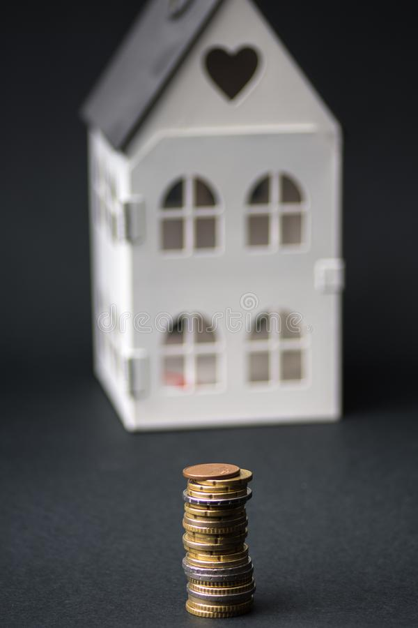 Money next to a small house.stack of euro coins, .mortgage concept royalty free stock images