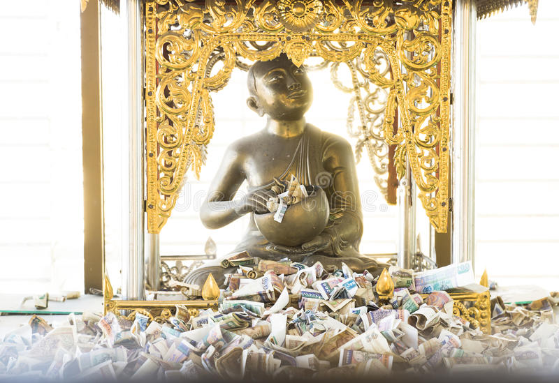 Money offerings for Buddha. Lots of Kyat bills in front of a golden Buddha, Myanmar royalty free stock image