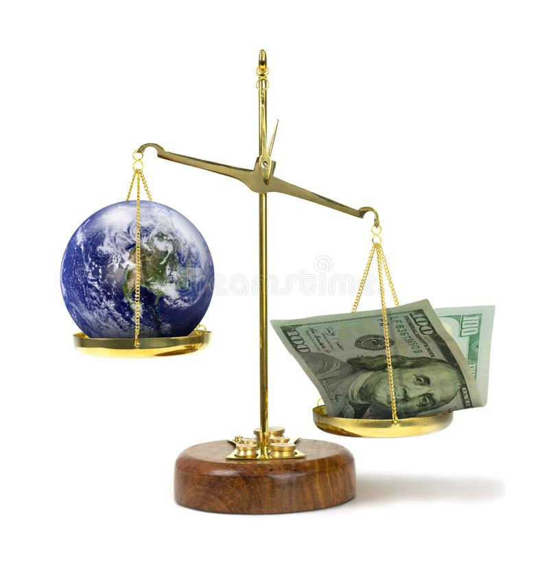 Money outweighing the earth on a scale representing greed & political corruption money being more powerful and important. U.S. money outweighing world on scale stock images