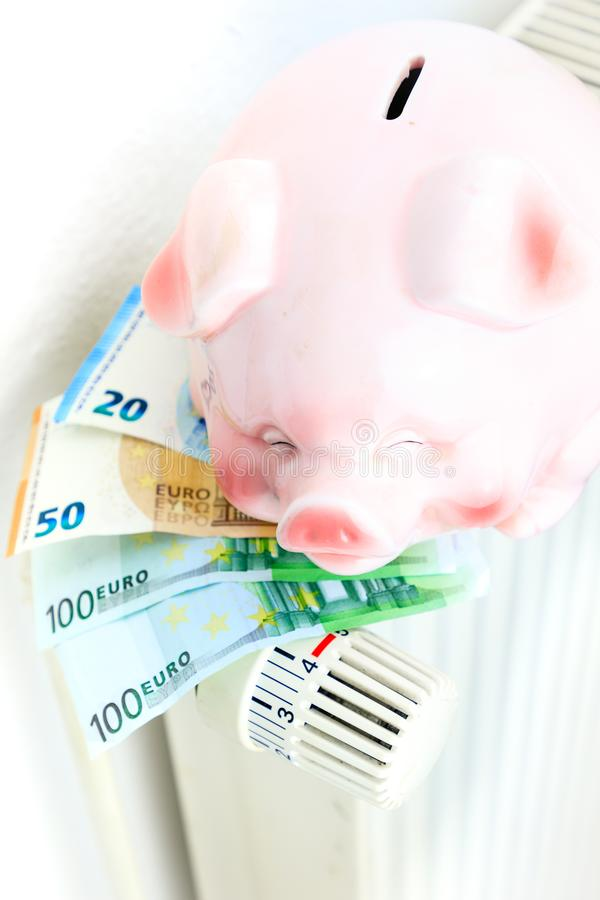 Money and piggy bank on a radiator symbolizes the expensive heat royalty free stock photography