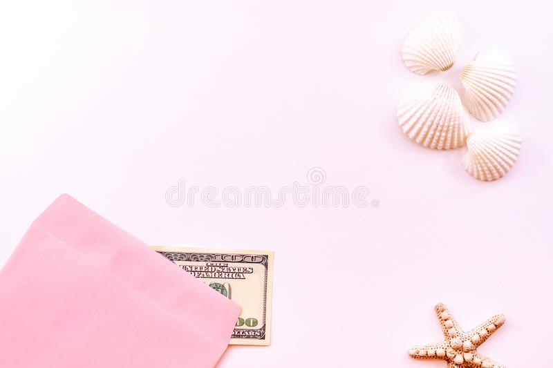 Money in a pink envelope, starfish, seashells on a pink background. Concept: Money for rest. Money in a pink envelope, starfish, seashells on a pink background stock photo