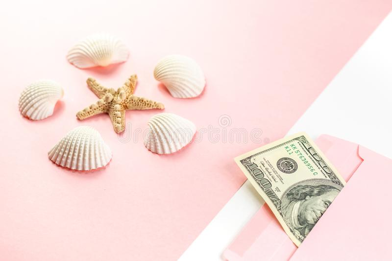 Money in a pink envelope, starfish, seashells on a blue background. Travel budget. Copy space, top view. stock photos