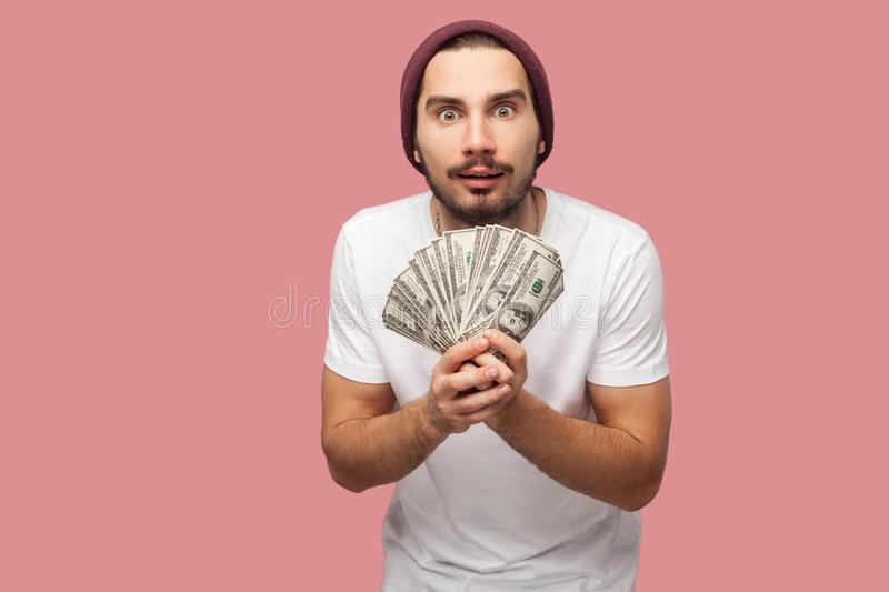 Money. Portrait of suprised handsome bearded young hipster man in white shirt and casual hat, stand, holding fan of dollars with stock photography