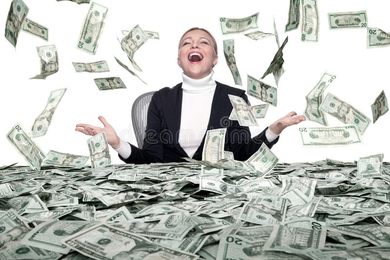 Money rain. Portrait of young woman sitting behind the table full of cash stock photography