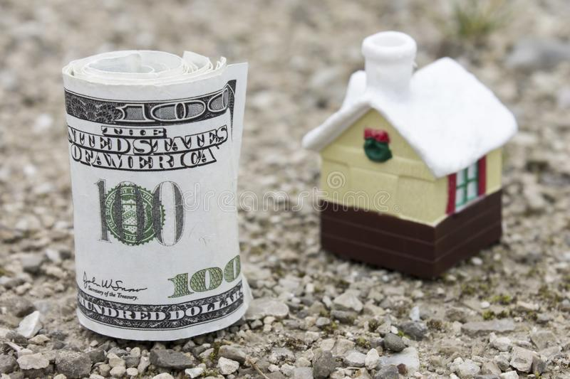 Money roll with small toy house on background. Real estate price concept. Selective focus royalty free stock photography