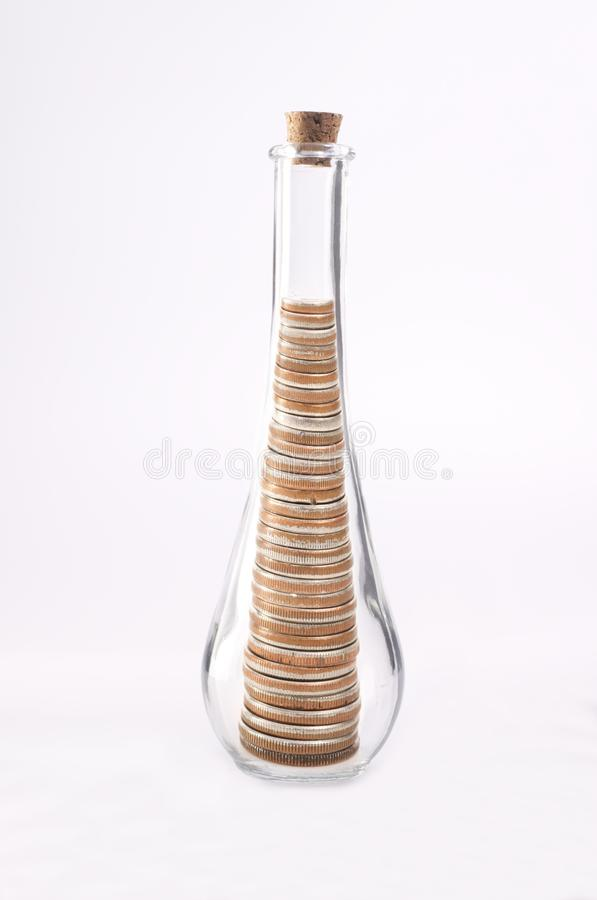 Money's Tight. Coins (quarters) are stacked inside a glass bottle with a tapered neck. The coins were altered to conform to the tapered neck. This is a concept royalty free stock photo