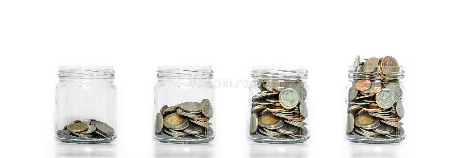 Money saving, glass jar arrange with coins inside growing, on white background stock images