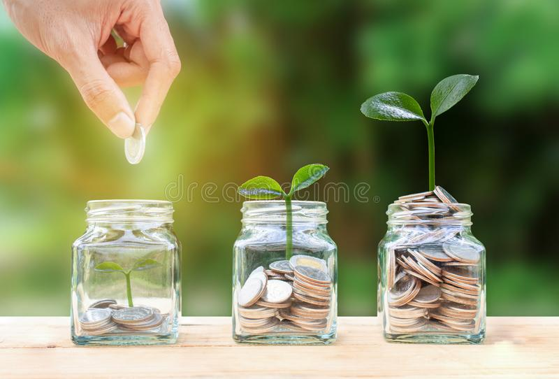 Money savings, investment, making money for future, financial wealth management concept. A man hand holding coin over stacked royalty free stock photography