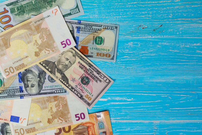 Money scattered randomly. On aquamarine wood board stock image