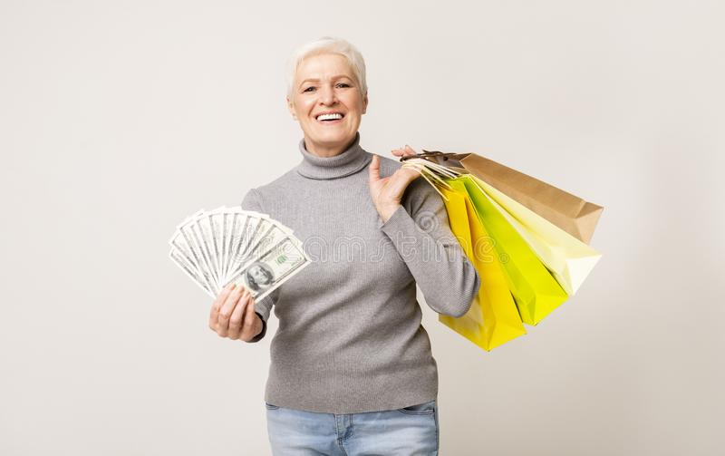 Cheerful Senior Woman Holding Bunch Of Money And Shopping Bags royalty free stock photos