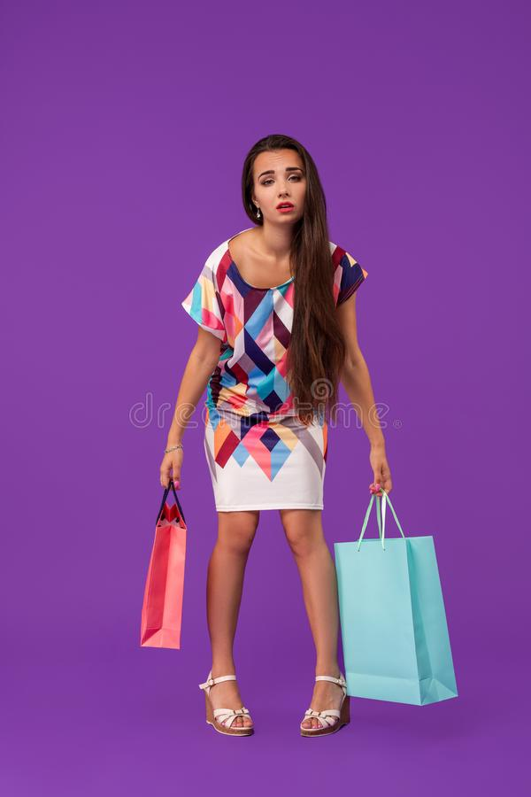 Lady with tired face. Girl stands on purple background holding shopping bags. Woman wears fashionable dress. Money and shopping concept. Lady with tired face royalty free stock images
