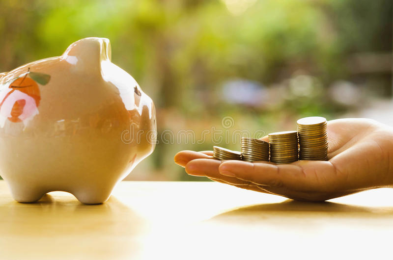 Money stack on hand and piggy bank save. Concept royalty free stock photo