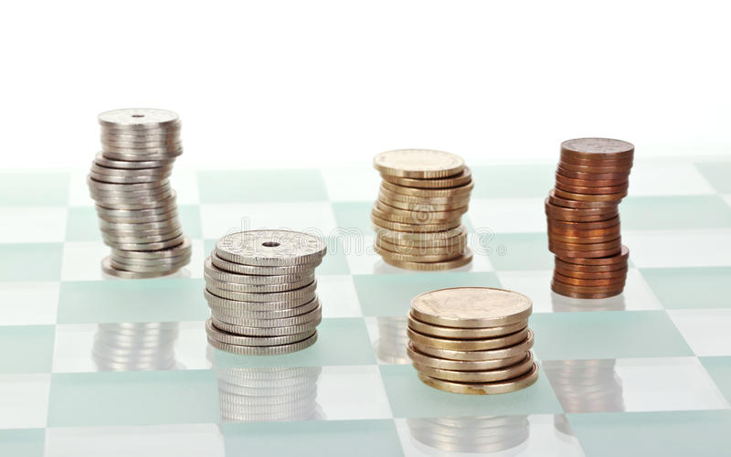 Money strategy. Concept with several stacks of money, placed on a chess board stock photos