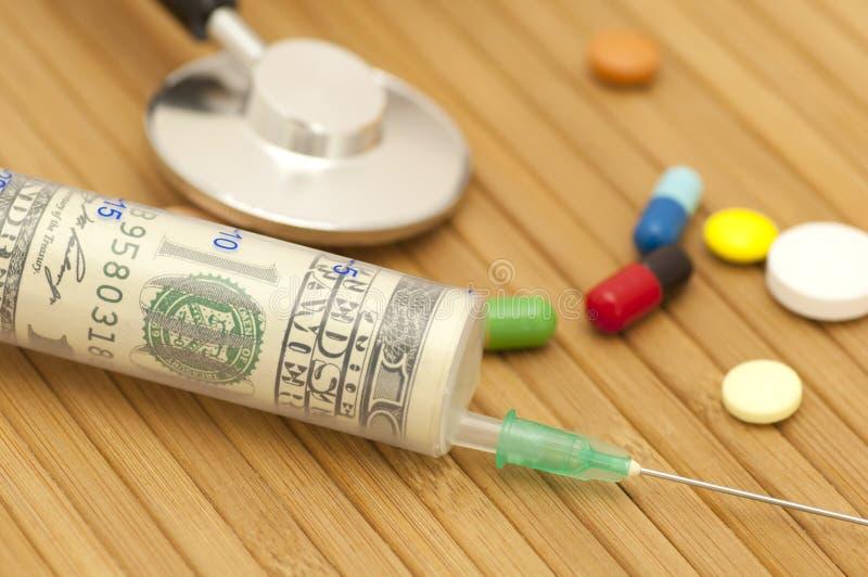 Money in syringe stock images