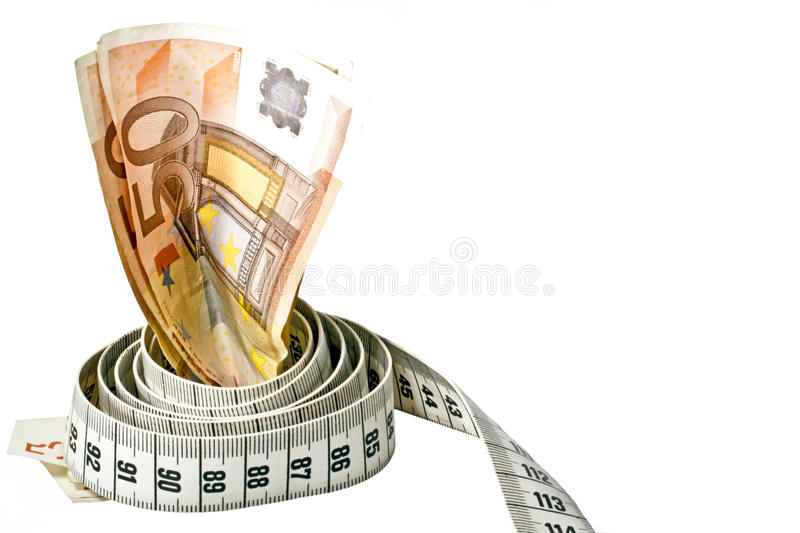 Money with a tape measure wrapped around it royalty free stock image