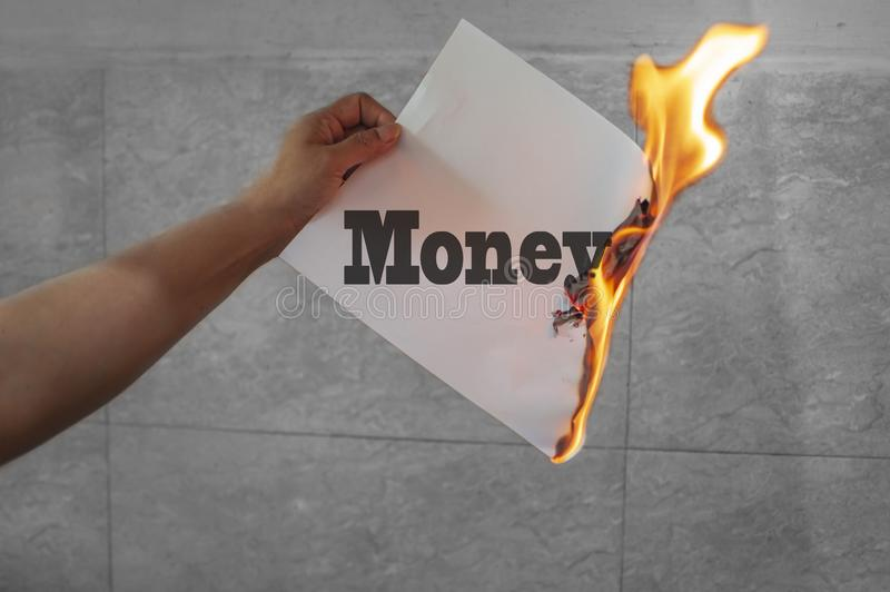 Money text on fire with burning paper. In hand stock illustration