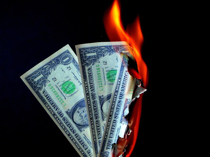 Money to Burn. Dollar bills in flames, illustrating financial problems such as inflation, depression, bankruptcy, waste royalty free stock photography