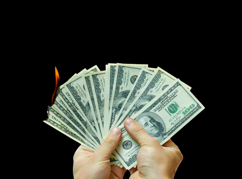 Money To Burn. A man holding multiple US hundred dollar bills that are starting to burn, isolated on a solid black background stock photography