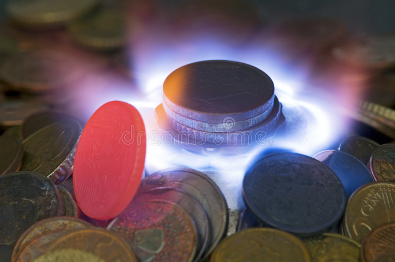 Money to Burn: Wasting Energy. A glowing red hot coin in front of the blue flames of burning natural gas, a metaphor of wasting energy, not only bad for the royalty free stock images
