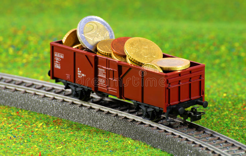 Money Transport. Miniature Wagon filled with Euro coins on on railway surrounded by grass royalty free stock photo