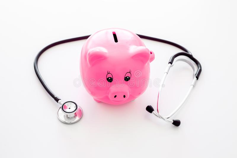 Money for treatment. Medical expenses. Moneybox in shape of pig near stethoscope on white background royalty free stock photo