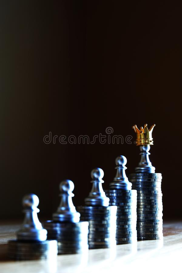 Money is a true king. Chess pawn stand on the highest coin stack wearing a crown. Wealthiness concept. Copy space stock image