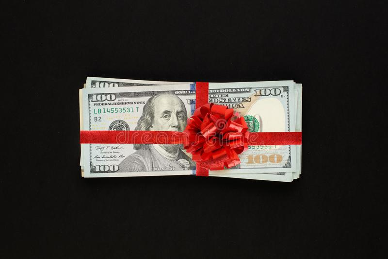 Money us dollars cash gift with red ribbon on black background. American Dollar 100 banknote gift profit concept.  royalty free stock image