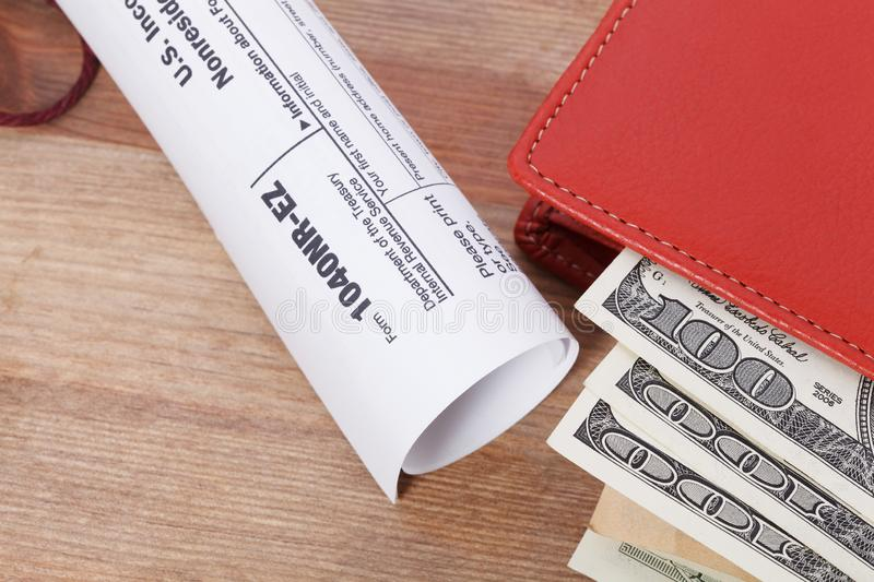 Money In Wallet and tax form with calculator on wooden table. Money In Wallet and tax form with calculator on wooden table royalty free stock photo