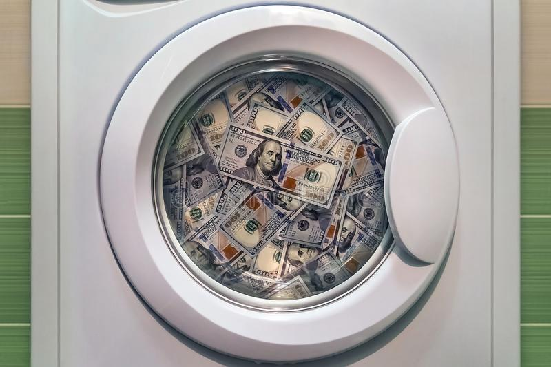 Money in washing machine close up. Concept of laundering illegal money. washing dirty American banknotes nominal value one hundred dollars royalty free stock photos