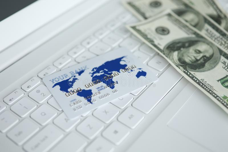 Money and white plastic card lie on keyboard of laptop. Currency on computer royalty free stock photography