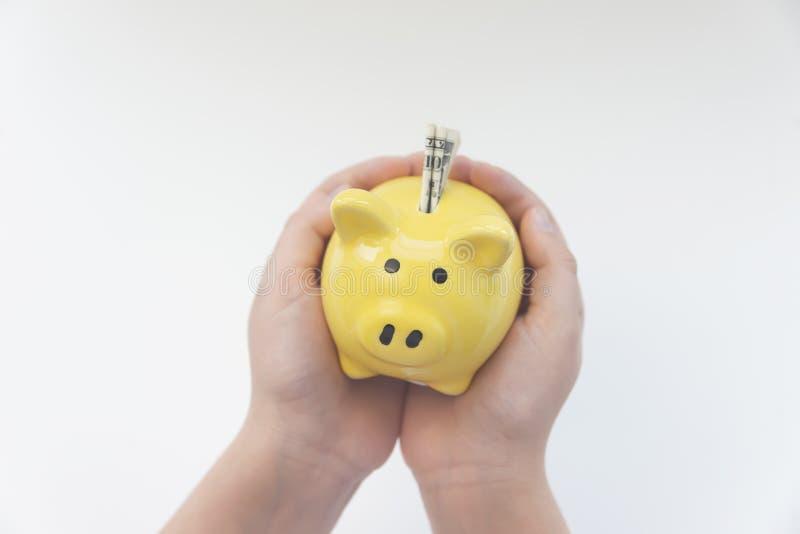 Moneybox amarillo del cerdo en las manos de un niño foto de archivo libre de regalías