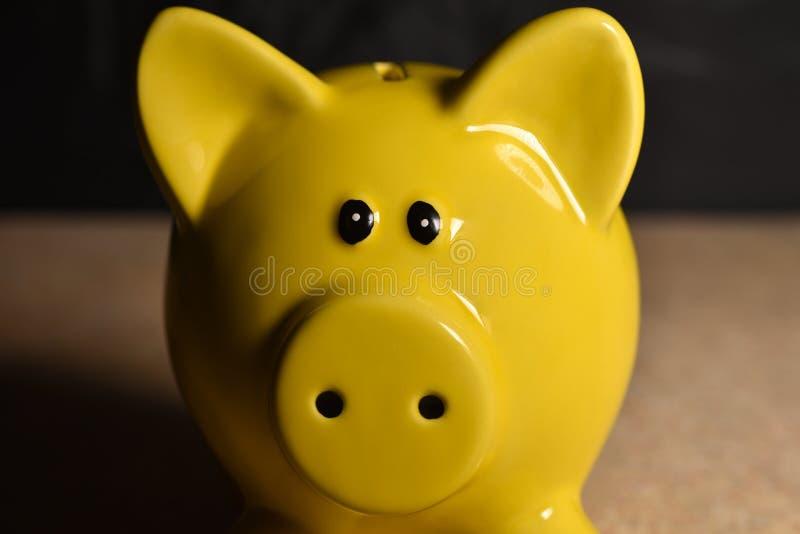 Moneybox amarillo del cerdo sin las monedas en un fondo negro foto de archivo libre de regalías