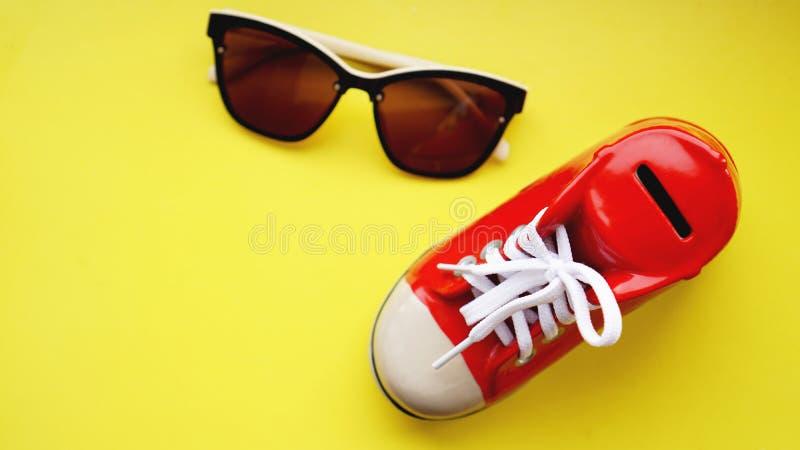 Moneybox bajo la forma de zapatillas de deporte Gafas de sol en un fondo amarillo imágenes de archivo libres de regalías