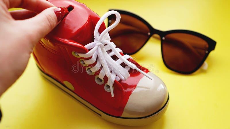 Moneybox bajo la forma de zapatillas de deporte Gafas de sol en un fondo amarillo fotos de archivo