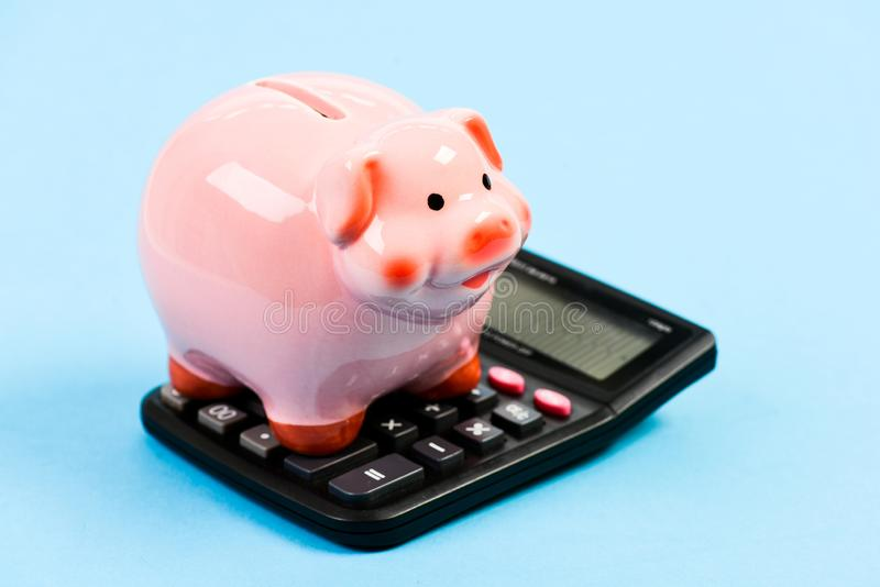 Moneybox with calculator. Piggy bank. bookkeeping. financial problem. planning and counting budget. money saving royalty free stock image
