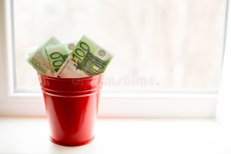 Moneybox, conta do Euro na cubeta na janela branca Fundo claro Lugar para o texto Vista superior fotografia de stock royalty free