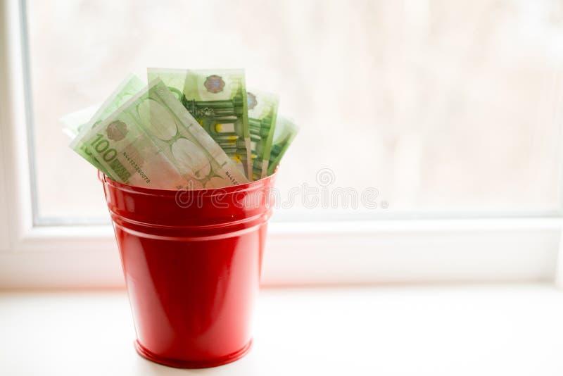 Moneybox, conta do Euro na cubeta na janela branca Lugar para o texto Vista superior Muito dinheiro fotografia de stock