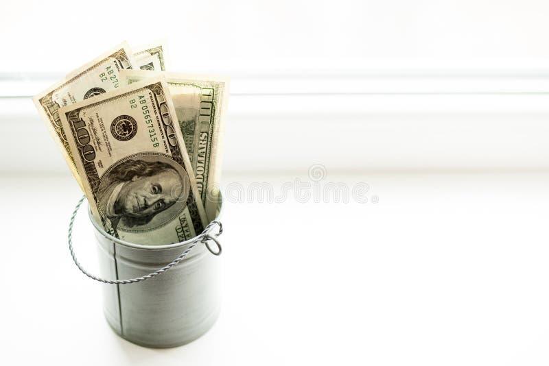 Moneybox, dolary w wiadrze na białym okno miejsce tekst Odgórny widok dużo pieniędzy obrazy stock