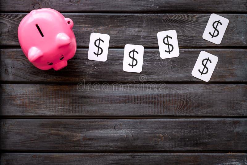 Moneybox en la forma de la muestra del cerdo y de dólar en copyspace de madera de la opinión superior del fondo imagenes de archivo