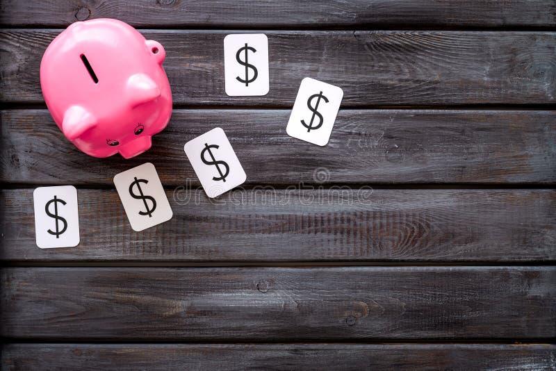 Moneybox en la forma de la muestra del cerdo y de dólar en copyspace de madera de la opinión superior del fondo fotografía de archivo