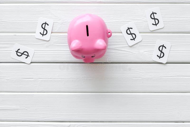 Moneybox en la forma de la muestra del cerdo y de dólar en el espacio de madera blanco de la opinión de top del fondo para el tex fotografía de archivo