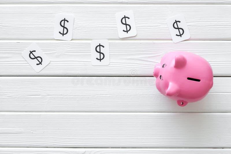 Moneybox en la forma de la muestra del cerdo y de dólar en el espacio de madera blanco de la opinión de top del fondo para el tex fotos de archivo libres de regalías